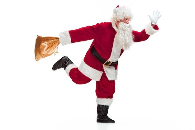 Retrato de hombre disfrazado de papá noel con una lujosa barba blanca, sombrero de papá noel y un traje rojo - en longitud completa corriendo y aislado en blanco
