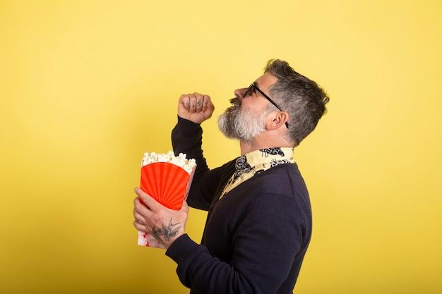 Retrato de un hombre divertido de barba blanca, aturdido, loco y sin palabras, sorprendido por el giro de la trama de la película que está mirando sosteniendo una caja de palomitas de maíz desde el perfil hasta la cámara sobre fondo amarillo.