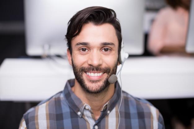 Retrato de hombre ejecutivo de servicio al cliente hablando por auriculares en el escritorio
