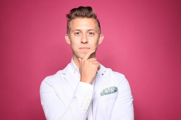 Retrato de hombre elegante sobre fondo rosa