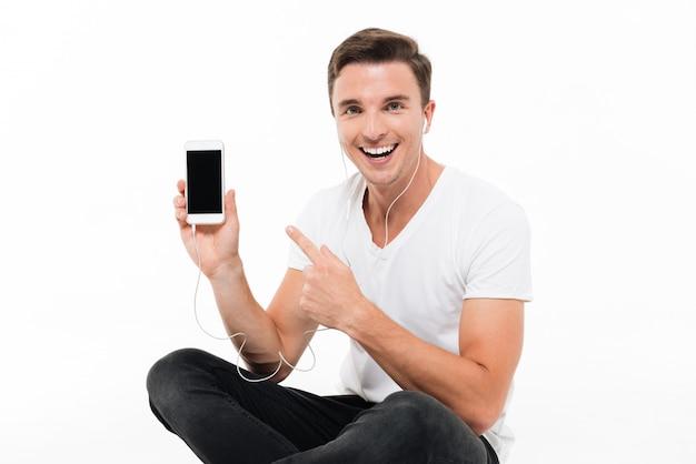 Retrato de un hombre emocionado feliz en auriculares apuntando con el dedo