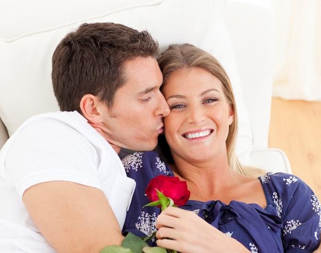 Retrato de un hombre encantador besando a su esposa tumbada en el sofá