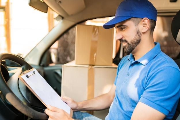 Retrato de un hombre de entrega comprobando la lista de entrega mientras está sentado en la furgoneta. concepto de entrega y envío.