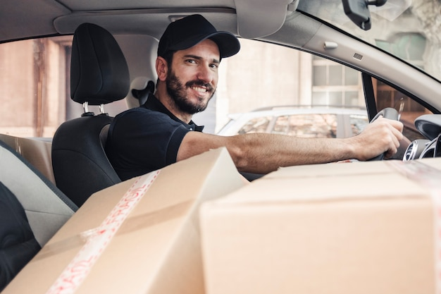 Retrato de un hombre de entrega feliz con paquetes en vehículo