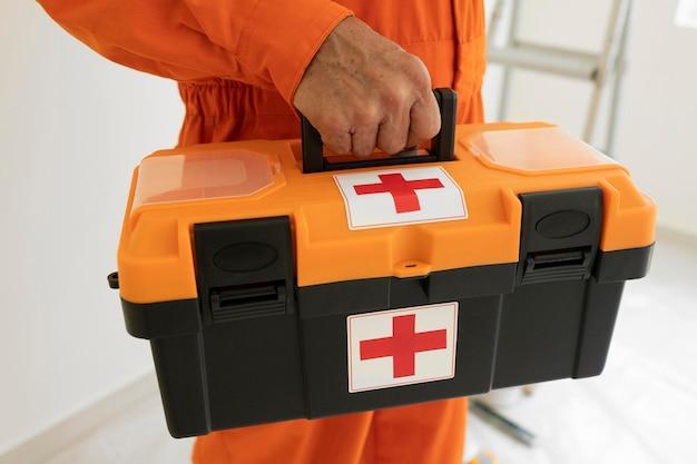 Retrato de hombre con equipo de protección de seguridad y botiquín de primeros auxilios