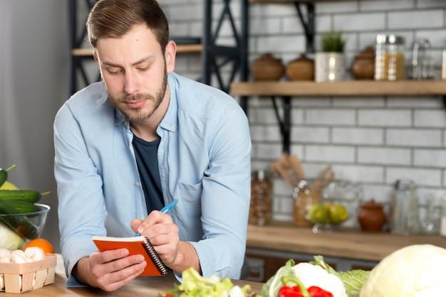 Retrato de un hombre escribiendo una receta en su diario en la cocina.