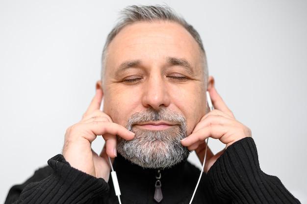 Retrato de hombre escuchando música con los ojos cerrados