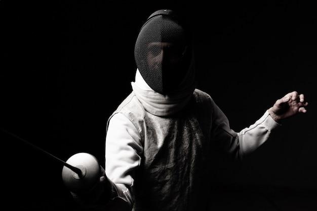 Retrato de hombre esgrimista en máscara y lámina realizando pelea