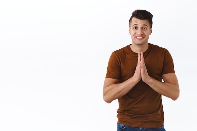 Retrato de hombre esperanzado lindo pegajoso pidiendo favor, tomados de la mano en oración, suplicando o pidiendo ayuda