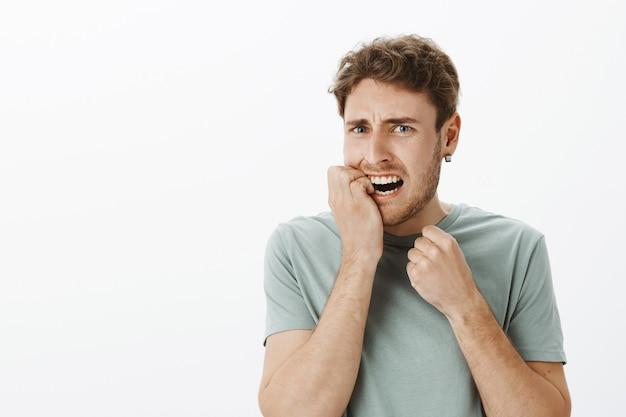 Retrato de hombre europeo ansioso estresado con cabello rubio, mordiéndose las uñas y frunciendo el ceño, haciendo muecas de miedo, nervioso y asustado