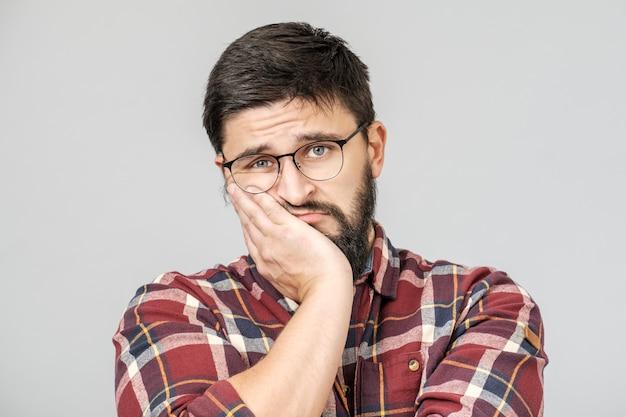 Retrato de hombre europeo determinado infeliz con mirada seria y preocupada sobre fondo gris