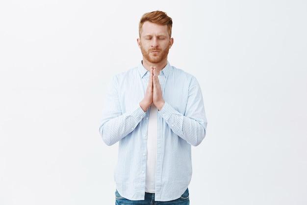 Retrato de un hombre europeo pelirrojo maduro de aspecto serio tranquilo en camisa, tomados de la mano en oración cerca del pecho, cerrando los ojos, orando en estilo asiático cerca del santuario sobre la pared gris