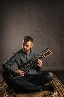 Retrato de un hombre europeo tocando el sitar sentado en la alfombra