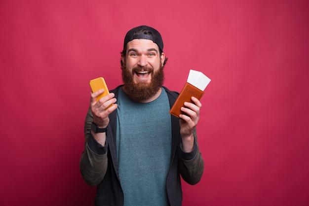 Retrato de un hombre excitado sosteniendo su pasaporte con boletos y su teléfono