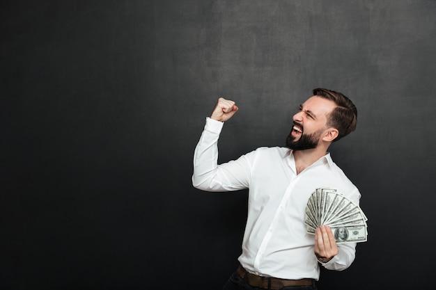 Retrato de hombre exitoso con camisa blanca regocijándose como ganador con un abanico de billetes de 100 dólares en la mano, apretando el puño a un lado sobre gris oscuro