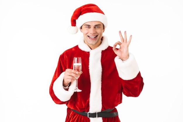 Retrato de hombre feliz de 30 años en traje de santa claus y sombrero rojo bebiendo champán de vidrio
