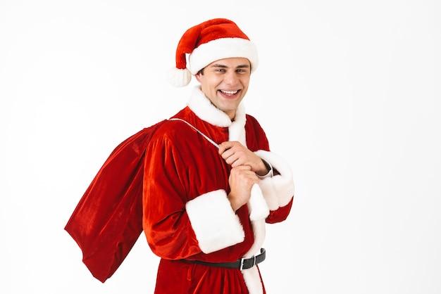 Retrato de hombre feliz de 30 años en traje de santa claus y sombrero rojo con bolsa de regalo sobre el hombro