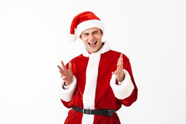Retrato de hombre feliz de 30 años en traje de santa claus y sombrero rojo riendo