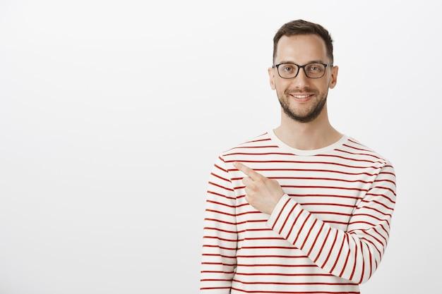 Retrato de hombre feliz aduly satisfecho con cerdas en gafas de moda y jersey de rayas