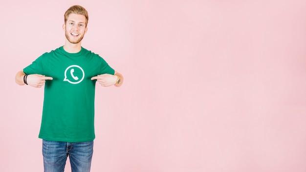 Retrato de un hombre feliz apuntando a su camiseta con el icono de whatsapp