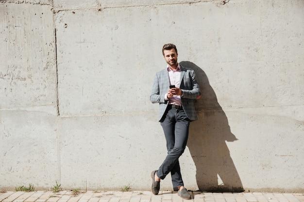 Retrato de un hombre feliz en chaqueta con teléfono móvil