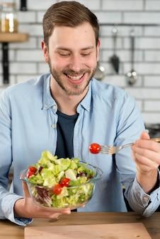 Retrato de un hombre feliz comiendo ensalada fresca saludable en el tazón de fuente
