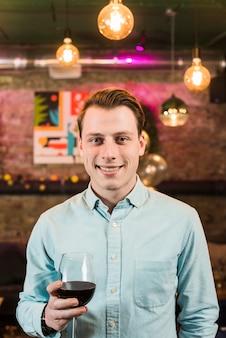 Retrato de un hombre feliz con copa de vino en club nocturno