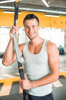 Retrato de un hombre feliz con correa de fitness en gimnasio