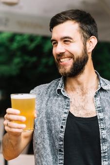 Retrato de un hombre feliz disfrutando el vaso de cerveza