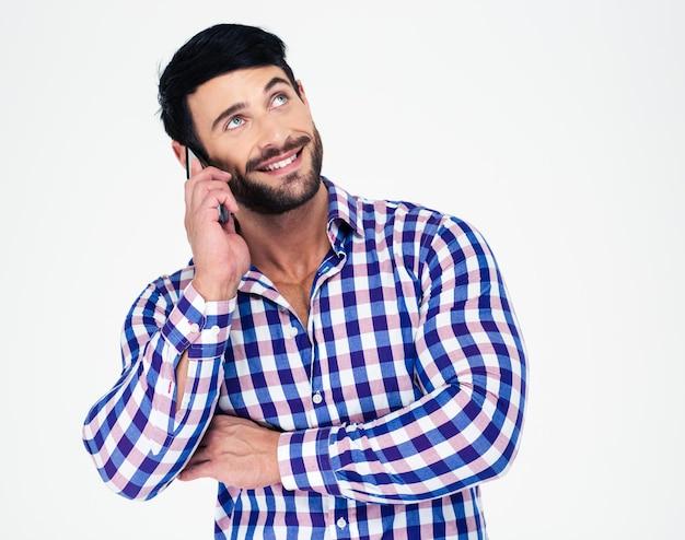 Retrato de un hombre feliz hablando por teléfono y mirando hacia arriba aislado en una pared blanca