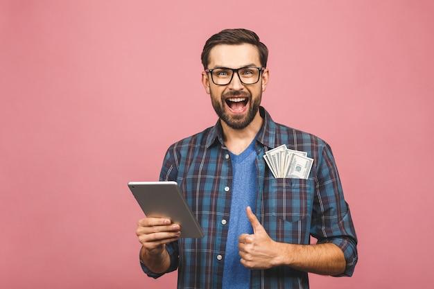 Retrato del hombre feliz hermoso joven con barba hipster en camisa a cuadros de pie, con tableta y dinero. fondo rosa pulgares hacia arriba.