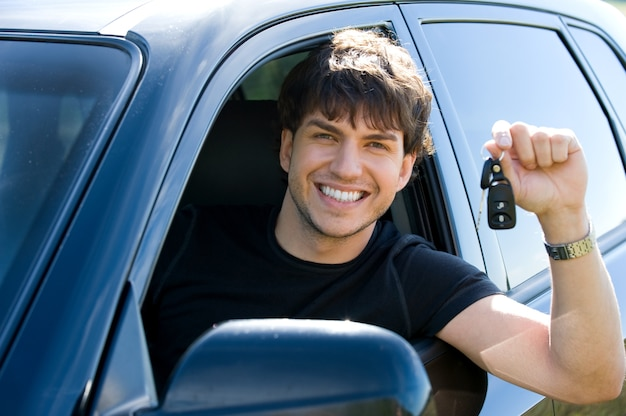 Retrato de hombre feliz joven exitoso mostrando las llaves sentado en coche nuevo