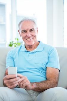 Retrato del hombre feliz mayor que usa smartphone mientras que se sienta en el sofá en casa