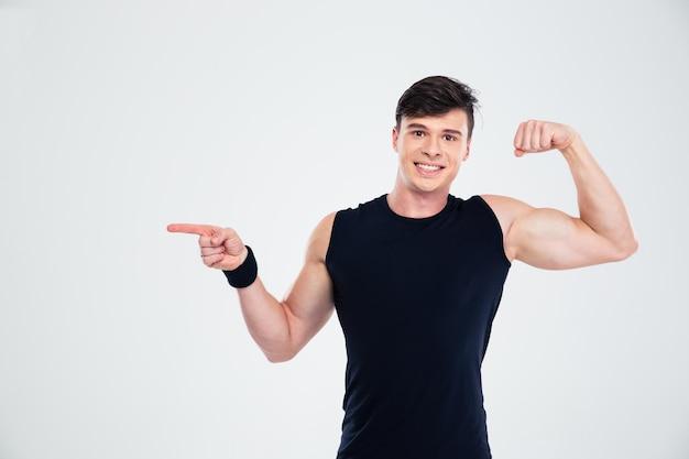 Retrato de un hombre feliz mostrando sus bíceps y señalar con el dedo en copyspace aislado