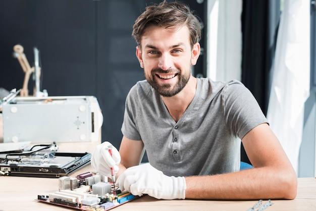 Retrato de un hombre feliz que repara la placa de circuito de la computadora