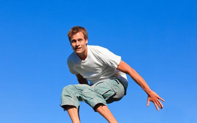 Retrato de un hombre feliz saltando en el aire al aire libre