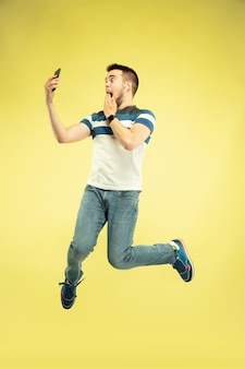 Retrato de hombre feliz saltando con gadgets en pared amarilla