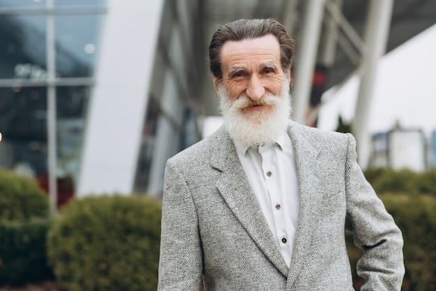 Retrato de hombre feliz senior en los edificios de oficinas con espacio de copia