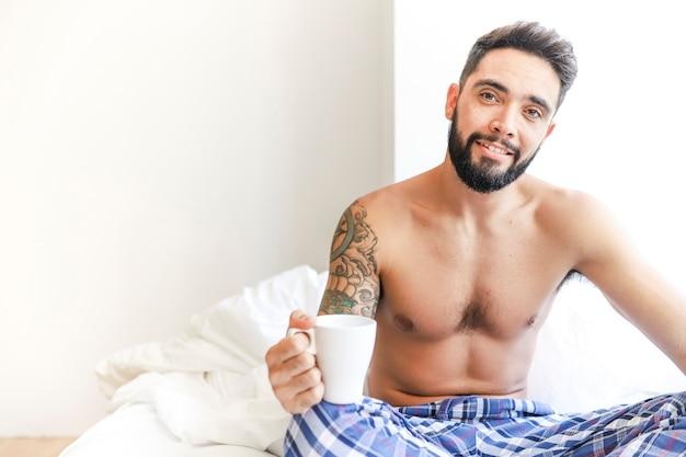 Retrato de un hombre feliz sentado en la cama sosteniendo una taza de café