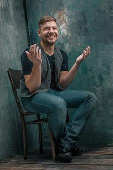 Retrato de hombre feliz sonriente sentado en la silla