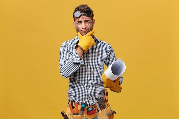Retrato de hombre fettler vistiendo ropa protectora sosteniendo un plano con expresión pensativa mientras piensa en sus acciones durante el trabajo. reparador con kit de instrumentos aislados sobre pared