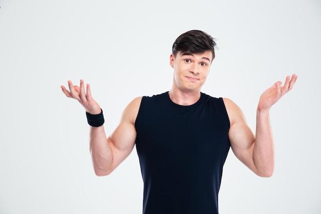 Retrato de un hombre de fitness encogiéndose de hombros aislado