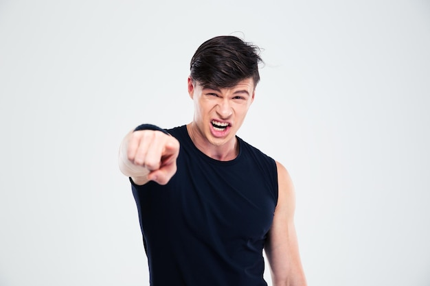 Retrato de hombre de fitness enojado apuntando con el dedo a la cámara aislada sobre un fondo blanco