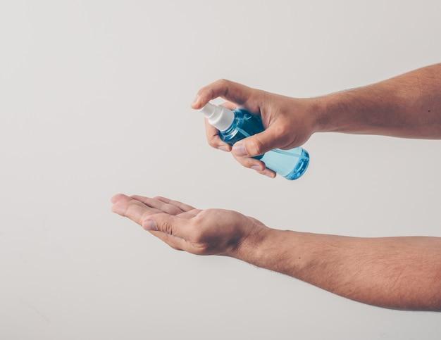 Retrato de un hombre en el fondo blanco desinfectando su mano