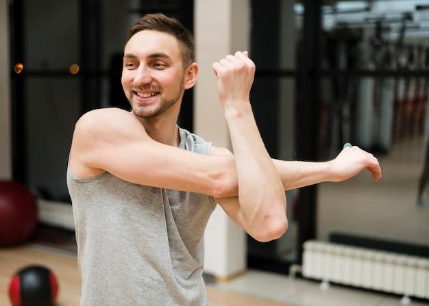 Retrato de hombre en forma estirando en el gimnasio