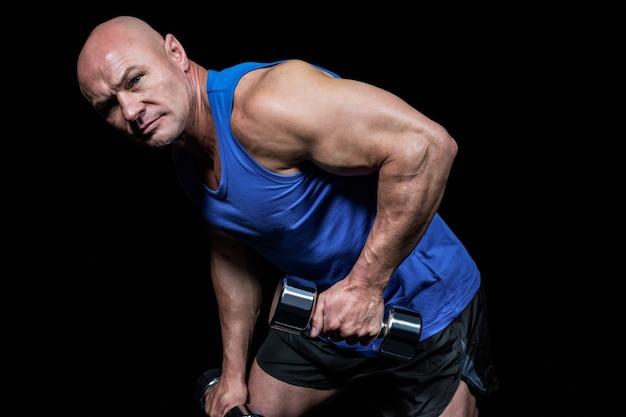 Retrato de hombre en forma haciendo ejercicio con pesas