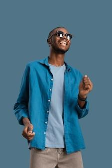 Retrato de hombre fresco con gafas de sol bailando