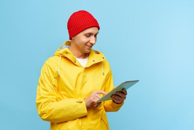 Retrato de hombre fresco positivo en otoño cálido ropa al aire libre superior con tableta
