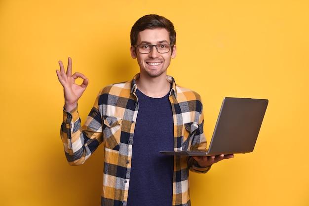 Retrato de hombre fresco seguro inteligente positivo en anteojos sosteniendo portátil, haciendo bien gesto con la mano aislado sobre fondo amarillo
