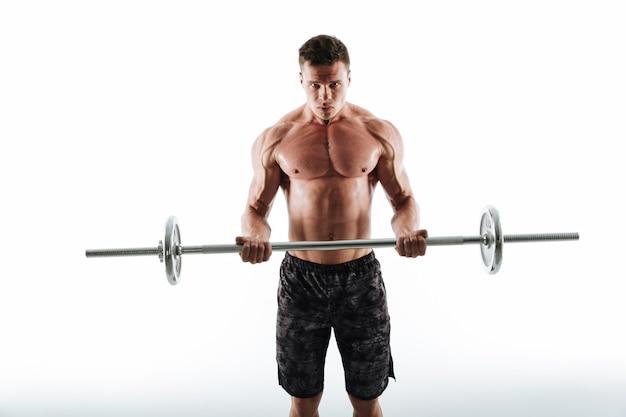 Retrato de hombre fuerte deportivo en shorts negros haciendo ejercicio con barra